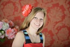 Glückliches schönes junges Mädchen mit einer Blume Lizenzfreie Stockfotos