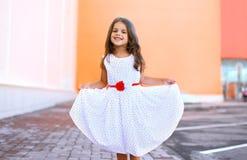 Glückliches schönes kleines Mädchen zeigt weißen Kleider- und Habenspaß stockfotografie