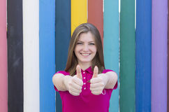 Glückliches schönes Mädchen, das Daumen zeigt Lizenzfreie Stockfotos
