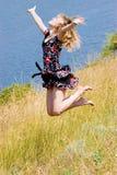 Glückliches schönes Mädchen, das in die Luft springt Stockfotografie