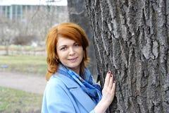 Glückliches schönes Mädchen, das großen Baum im Park umarmt Lizenzfreie Stockfotografie