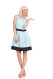 Glückliches schönes Mädchen im hellblauen Farbkleid, das Produkt darstellt Stockfoto