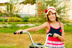 Glückliches schönes Mädchen mit Fahrrad auf Sonnenuntergang lizenzfreies stockbild