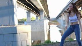 Glückliches schönes Mädchentanzen auf Hintergrund der Brücke stock footage