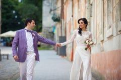 Glückliches schönes Paar-, Braut- und Bräutigamhändchenhalten in einem stree Stockbilder