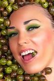 Glückliches schönes weibliches Gesicht in der Stachelbeere Stockfotografie