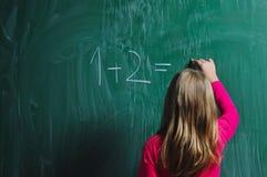 Glückliches Schulemädchen auf Mathekategorien Stockbild