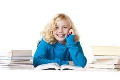 Glückliches Schulmädchen, das auf dem Fußboden tut Heimarbeit liegt Lizenzfreie Stockfotos