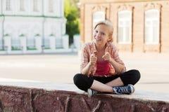 Glückliches Schulmädchen, das auf der Stadtstraße sitzt stockfotografie