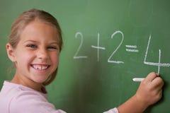 Glückliches Schulmädchen, das eine Zahl schreibt Lizenzfreies Stockfoto