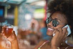 Glückliches schwarzes Mädchen, das im Café mit Glas Wein lächelt lizenzfreie stockfotos