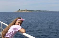 Glückliches Segeln des kleinen Mädchens in einem Boot, das in dem Meer auf Sommerkreuzfahrt lächelt stockfotos