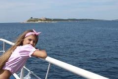 Glückliches Segeln des kleinen Mädchens in einem Boot, das in dem Meer auf Sommerkreuzfahrt lächelt stockfoto