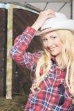 Glückliches sexy blondes Cowgirl, das innerhalb des Gutshauses lächelt Stockfotografie