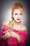 Glückliches sexy schönes blondes Mädchen im rosa Kleid mit Frisur und helles Make-up und Parfümflasche Lizenzfreies Stockbild