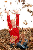 Glückliches sieben Einjahresmädchen, das im Stapel der Blätter spielt stockfotografie