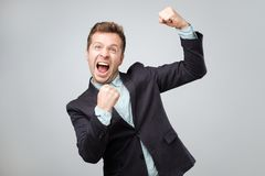 Glückliches Siegerkonzept Emotionaler kaukasischer Mann in der Klage ist glücklich und froh, weil er viel Geld gewann stockfotografie