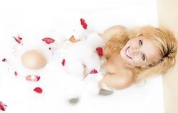 Glückliches sinnliches anziehendes kaukasisches blondes in der schäumenden Badewanne gefüllt mit Rose Petal Lizenzfreies Stockfoto