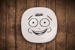 Glückliches smileykarikaturgesicht auf bunter Tellerplatte Lizenzfreie Stockfotografie
