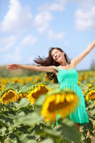 Glückliches sorgloses Sommermädchen im Sonnenblumenfeld Stockbild