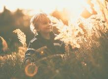Glückliches Spielen des kleinen Jungen im Freien in der schönen Herbstlandschaft Lizenzfreie Stockbilder