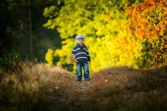 Glückliches Spielen des kleinen Jungen im Freien in der schönen Herbstlandschaft Stockbilder