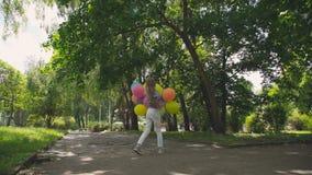 Glückliches, spielerisches Mädchen freut sich mit bunten Ballonen auf dem Weg im sonnigen Park stock video footage