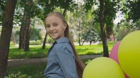 Glückliches, spielerisches Mädchen wirft mit bunten Ballonen auf dem Weg im sonnigen Park auf stock footage