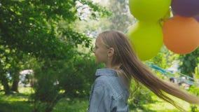 Glückliches, spielerisches Mädchen wirft mit bunten Ballonen auf dem Weg im sonnigen Park auf stock video footage