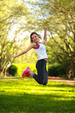 Glückliches sportives Mädchen, das in grünen Sommerpark springt lizenzfreie stockbilder