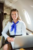 Glückliches Stewardess mit Laptop im Privatjet Lizenzfreie Stockfotos