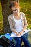 Glückliches Studentenmädchen, das zum Notizbuch am Campus schreibt Stockbild