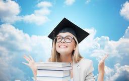 Glückliches Studentenmädchen in der Junggesellekappe mit Büchern Stockbilder