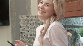Glückliches Tanzen der jungen Frau in der Küche, die zu Hause Musik auf Smartphone und Kaffee hört stock video footage