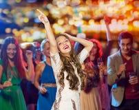 Glückliches Tanzen der jungen Frau am Nachtclub stockbild