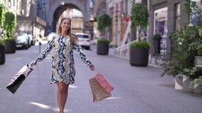 Glückliches Tanzen der jungen Frau an der Straße mit Einkaufstaschen Zeitlupeschuß 4K stock video footage
