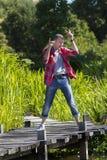 Glückliches Tanzen des jungen Mannes auf Zufriedenheit der Holzbrücke zum Spaß lizenzfreie stockfotos