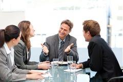 Glückliches Team, das zusammen bei einer Sitzung lacht lizenzfreies stockfoto