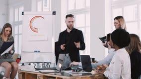 Glückliches Team von Geschäftsleuten hören auf mittleren gealterten Sprechermann am gesunden Büroarbeitsplatz Zeitlupe ROTES EPIC stock video footage