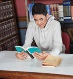 Glückliches Teenager-Lesebuch bei Tisch Lizenzfreie Stockbilder