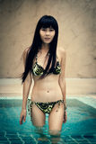 Glückliches thailändisches weibliches Genießen im Swimmingpool Lizenzfreie Stockfotografie