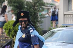 Glückliches tourister Fußballfan im nationalen russischen Militärwinterhut mit Kokardehut-ushanka lizenzfreie stockbilder