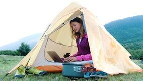 Glückliches touristisches Mädchen benutzt einen Laptop in einem Zelt, Freiberuflerdrucke in der Natur auf einer Reise stock footage