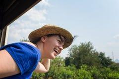 Glückliches touristisches Mädchen, welches die Fahrt in einem Zug genießt Lizenzfreie Stockfotos