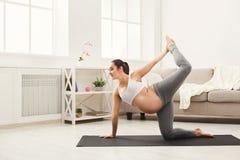 Glückliches Trainingsyoga der schwangeren Frau zu Hause stockfotografie