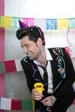 Glückliches trinkendes alleine genießen des jungen Mannes der Party lizenzfreies stockfoto