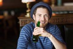 Glückliches trinkendes Bier des jungen Mannes an der Bar oder an der Kneipe Lizenzfreie Stockfotografie
