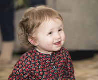 Glückliches u. hübsches Kleinkind mit Brown-Augen u. -geblümtem Kleid Stockfotografie