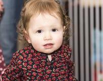 Glückliches u. hübsches Kleinkind mit Brown-Augen u. -geblümtem Kleid Lizenzfreies Stockfoto
