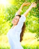 Glückliches und lächelndes Brunettemädchen mit dem gesunden Lächeln, das im Sommerpark sich entspannt stockbilder